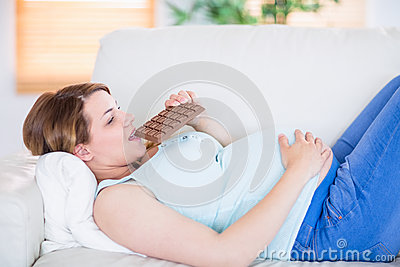 Pretty pregnant woman eating big bar of chocolate