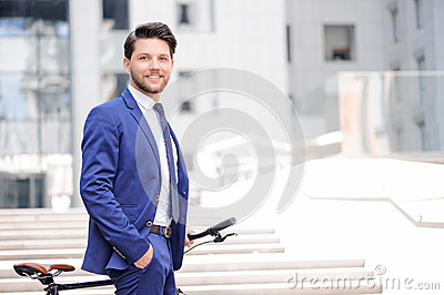 Pleasant businessman standing with bicycle