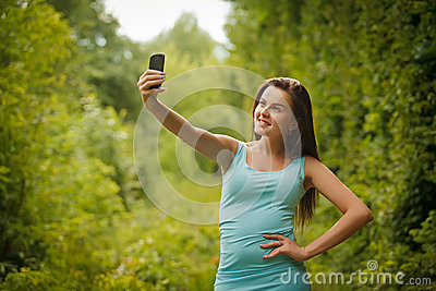 Cute smiling young Caucasian teenage girl taking a selfie outdoo
