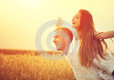 Happy couple having fun outdoors on wheat field