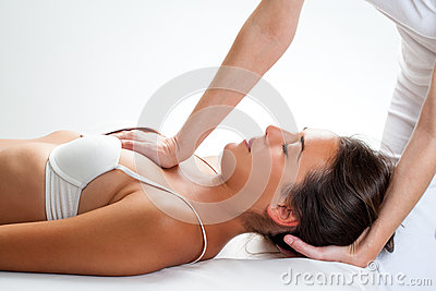 Physiotherapist doing thorax manipulation on woman.