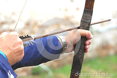 Businessman holding bow and shooting to archery target.