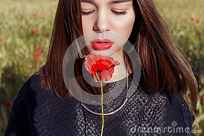 Beautiful cute girl with big lips and red lipstick in a black jacket with a flower poppy standing in a poppy field at sunset