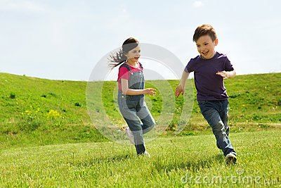 Happy little boy and girl running outdoors