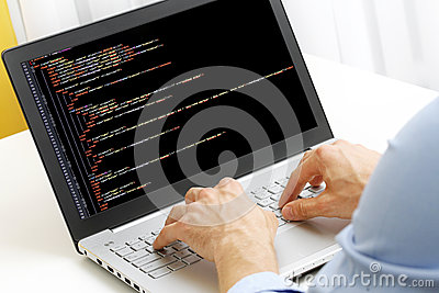 Programmer profession - man writing programming code on laptop