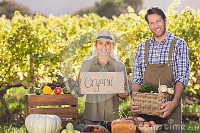 Farmer couple holding a basket and organic sign