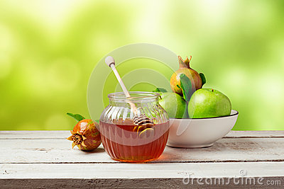 Honey jar and fresh apples with pomegranate over green bokeh background