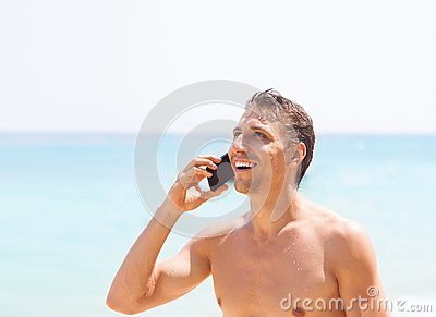 Man cell phone call smile on beach summer vacation