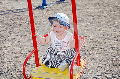 Little girl baby in a cap plays with toys in a sandbox with sand on the playground