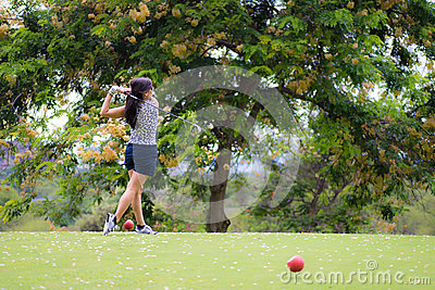 Female golfer hits golf ball
