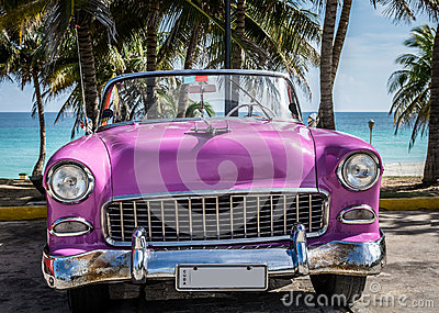 HDR Cuba pink american classic car parked under palms near the beach in Varadero