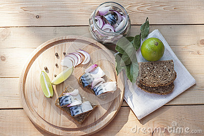Slices of marinated mackerel with onion in a jar, lime, laurel and bread on wooden board