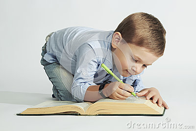 Little boy with book on the floor. funny child writer