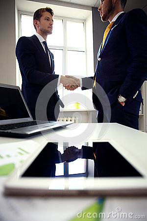 Close-shot of a tablet computer with businessmen handshaking