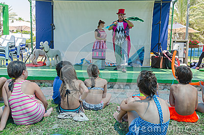 Omer (Beer-Sheva), ISRAEL -Two clowns on stage near the pool in front of children, seen from behind, July 25, 2015