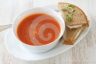 Tomato soup in white bowl with sandwich