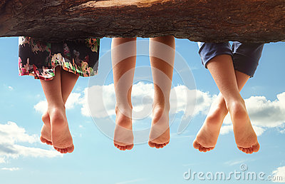 Children sitting in a tree dangling their feet