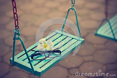 Vintage color tone style, glasses and white flower on the blue swing in evening