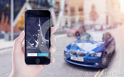 Uber application startup on Apple iPhone display in female hand