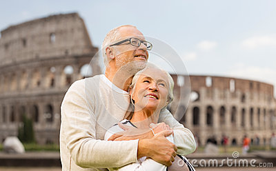 Happy senior couple over coliseum in rome, italy