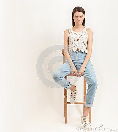 Full length portrait of young calm beautiful brunette woman posing for model tests against white background sitting on bar stool