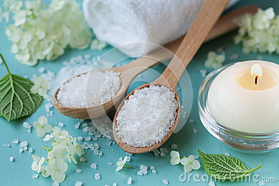 Spa composition with sea salt in wooden spoon, bath towel, white flowers and burning candles on a blue wooden surface