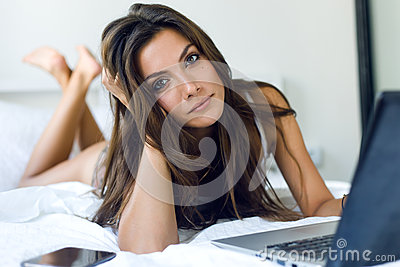 Beautiful young woman using her laptop in the bed.