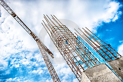 Concrete pillars on industrial construction site. Building of skyscraper with crane, tools and reinforced steel bars