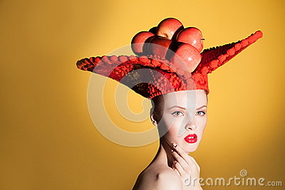 Creative beauty portrait of young beautiful woman looking at camera and posing in studio at big red hat with red apples.