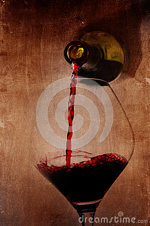 Man hand holding Bottle pouring red wine filling Glass on arty background