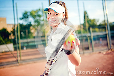 Woman playing tennis, holding racket and ball. Attractive brunette girl wearing white t-shirt and cap on tennis court