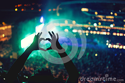 Heart shaped hands at concert, loving the artist and the festival. Music concert with lights and silhouette of a man enjoying
