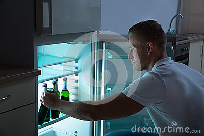 Man Removing Beer Bottle From Refrigerator