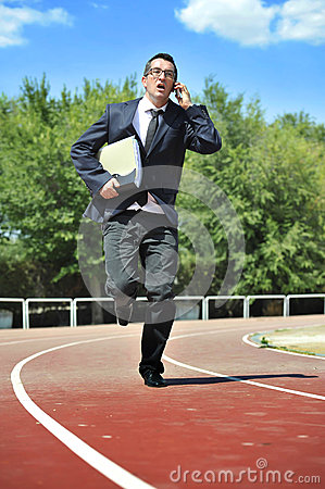 Businessman in suit and necktie carrying folder portfolio and files running in stress on athletic track talking on mobile phone