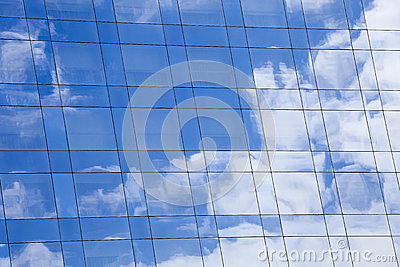 Sky and clouds background reflected on the glass mirror surface of a modern building