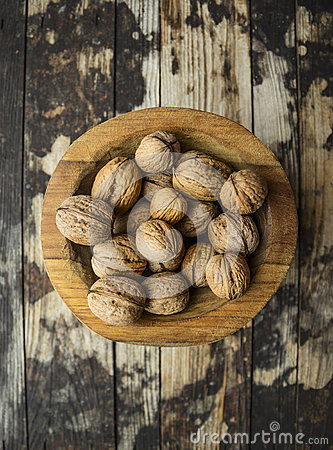 Walnuts in a wooden bowl on wooden rustic background, top view