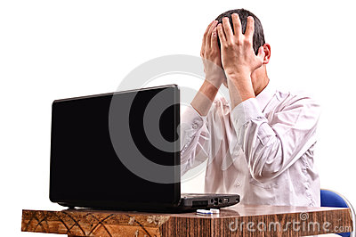 Frustrated young man, holding his head in front of a laptop in t