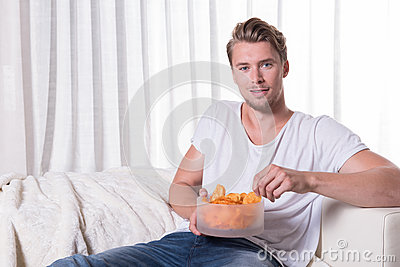 Portrait young man sitting on couch and eating chips