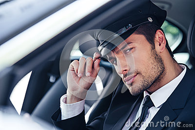 Handsome male chauffeur sitting in a car