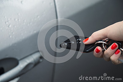 Woman using central locking remote to open car door.