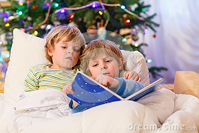 Two little blond sibling boys reading a book on Christmas
