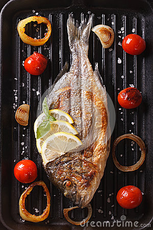 Dorado fish with vegetables closeup on the grill. Vertical top v