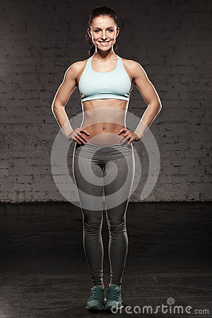 Sporty woman with a beautiful smile, fitness female with muscular body, do her workout, abdominals