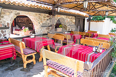 Colorful traditional red tablecloths on wooden tables and benches, old Bulgarian restaurant