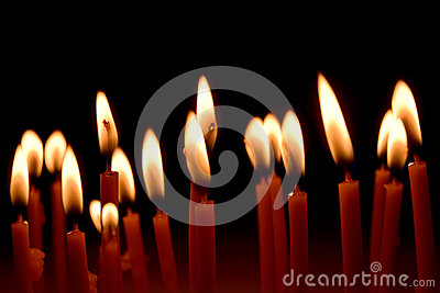 Close up view of the candles burning brightly in the dark.