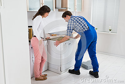 Worker Repairing Dishwasher While Woman In Kitchen