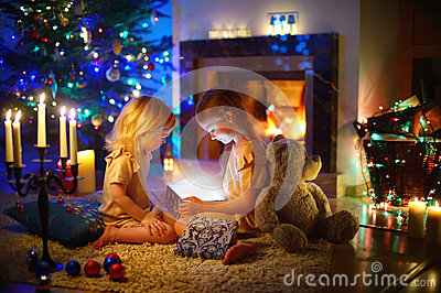 Little girls opening a magical Christmas gift