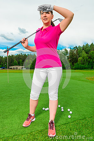 Beautiful woman on golf course looking behind flying ball