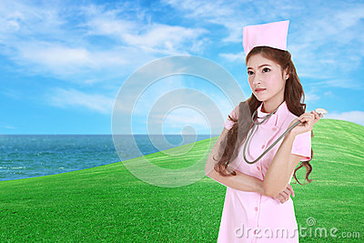 Female nurse with stethoscope with green grass field