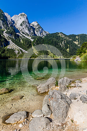 Beautiful landscape of alpine lake with crystal clear green water and mountains in background, Gosausee, Austria